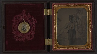 [Unidentified African American boy standing in front of painted backdrop showing American flag and tents ; campaign button with portraits of Lincoln on one side and Johnson on the opposite side are attached to inside cover of case] (LOC) | by The Library of Congress