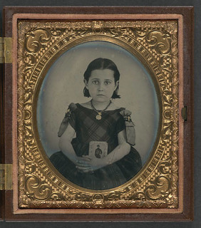 [Unidentified girl in mourning dress holding framed photograph of her father as a cavalryman with sword and Hardee hat] (LOC) | by The Library of Congress