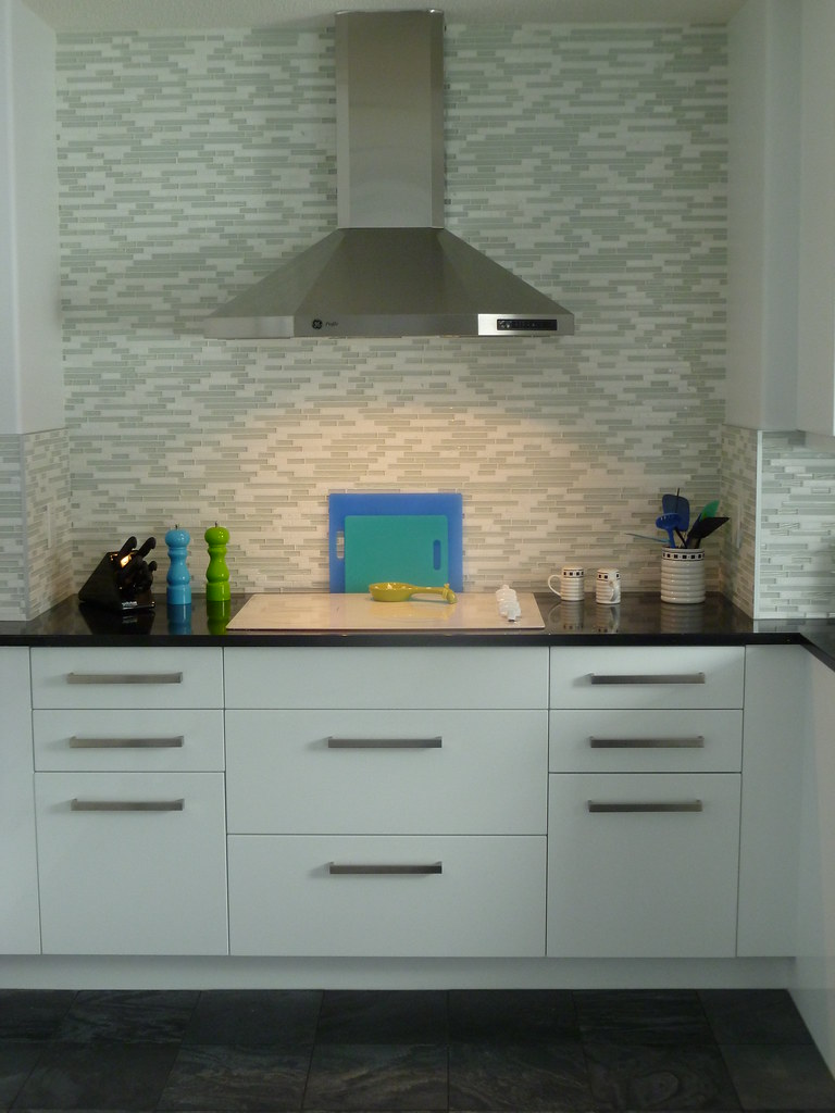 Marble and glass backsplash with quartz countertop. Honed