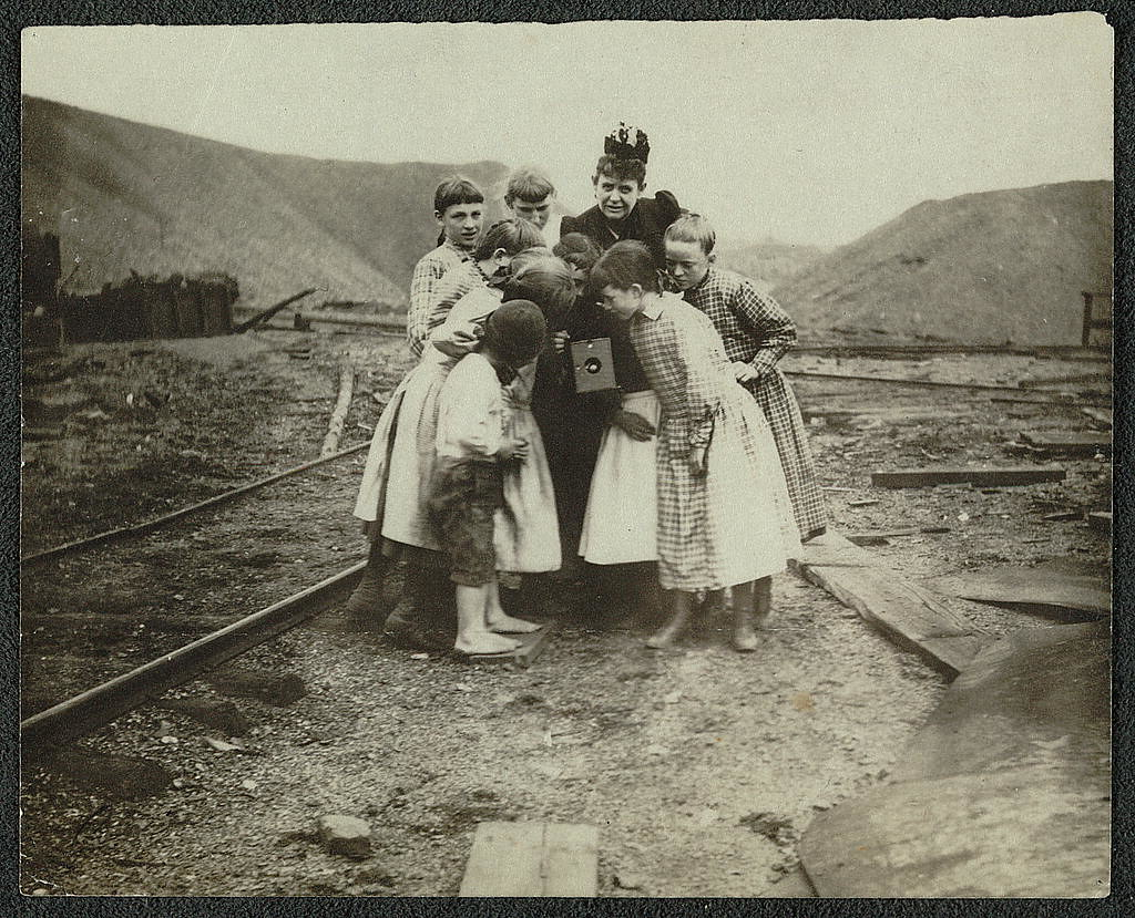 A Kodak creates a sensation, [between 1890 and 1910]. Frances Benjamin Johnston with group of children looking at her camera.