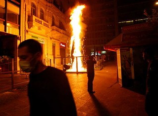 Greek civilian walks pass flames burning in Athens amid unrest aimed at stopping the imposition of further austerity measures designed to stave off the capitalist economic crisis. Parliament voted in favor of further measures against workers and youth. | by Pan-African News Wire File Photos