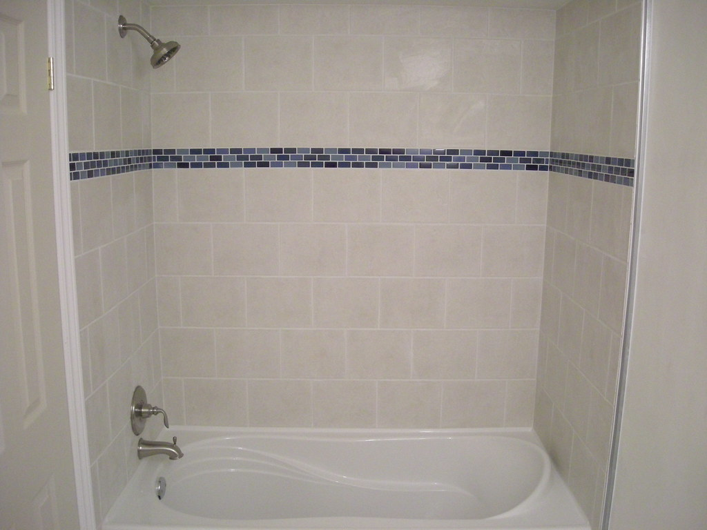 Ceramic tile shower and bathtub surround with glass border for Glass tile border bathroom ideas