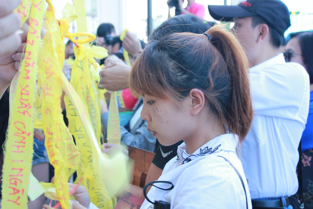 遊行開始前,移工團體將寫有各種語言版本的「廢除三年出國一日」訴求的黃絲帶綁在竹竿上。(攝影:張宗坤)