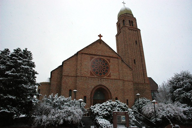 Saint John The Evangelist Catholic Church Under A Snowfall Brick With Cross Topped Tower