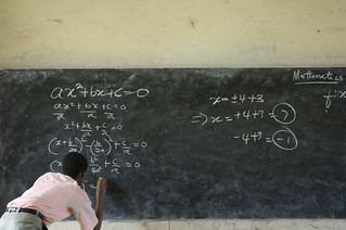 A student solves a mathematics equation at the Mfantsipim Boys School in Cape Coast | by World Bank Photo Collection