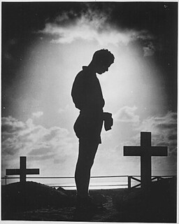 A Coast Guardsman stands in silent reverence beside the resting place of a comrade., 1944 | by The U.S. National Archives