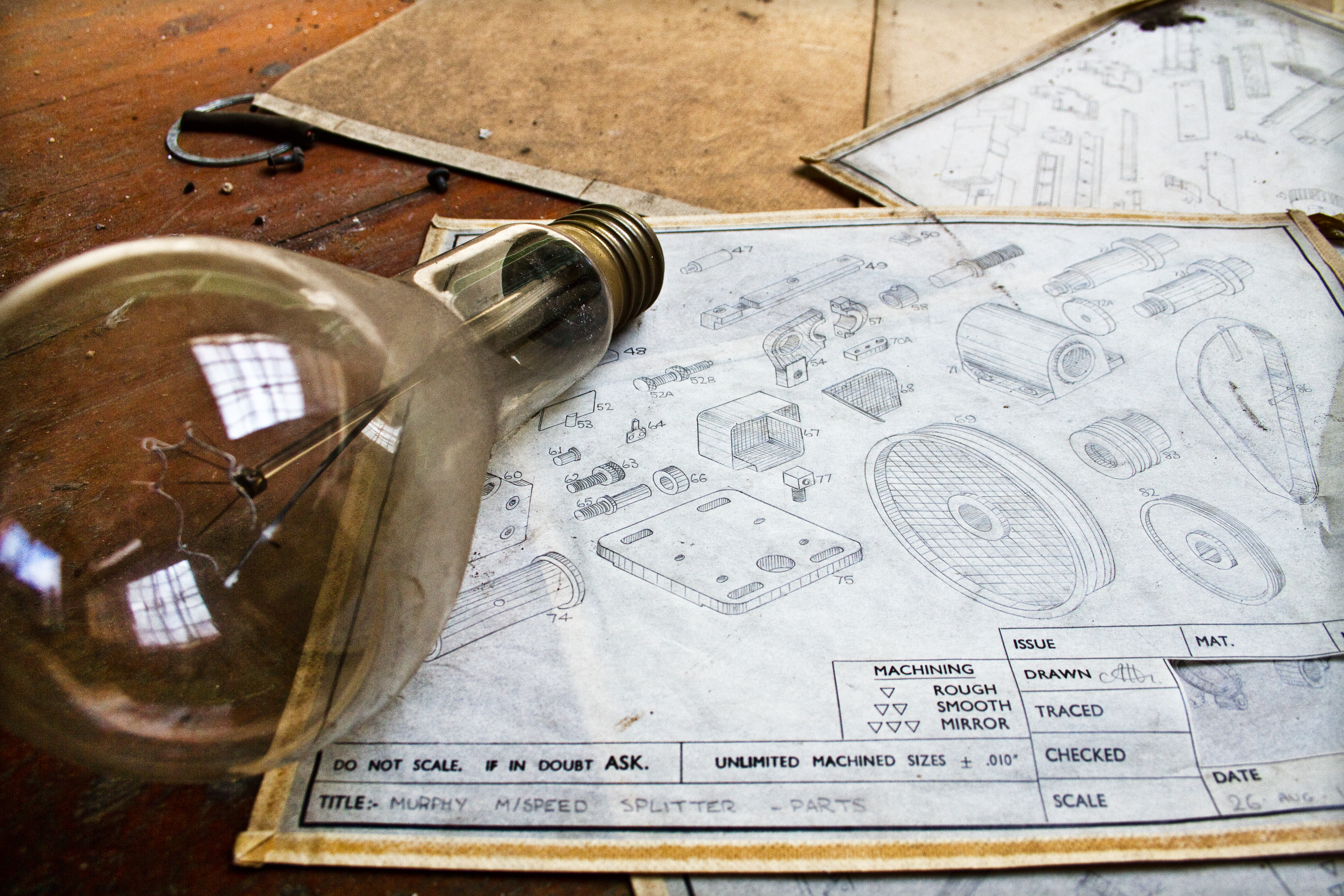 Image of hand-drawn machine schematics, scattered on a wooden table, with an antique lightbulb laying on the table in the foreground
