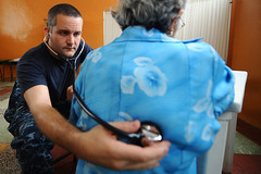 Navy doctor/Maryland cardiologist listens to a patient's lungs in Ecuador