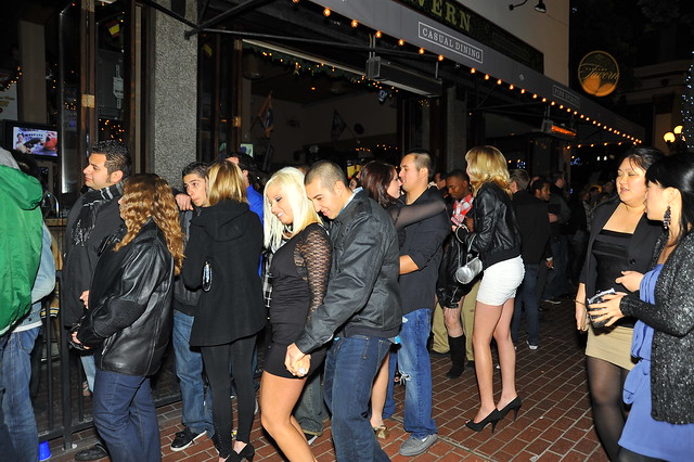 Is a waiting line to enter a club they are dancing even at sidewalk