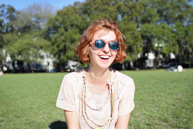 Junge Frau mit Sonnenbrille auf einer Sommerwiese