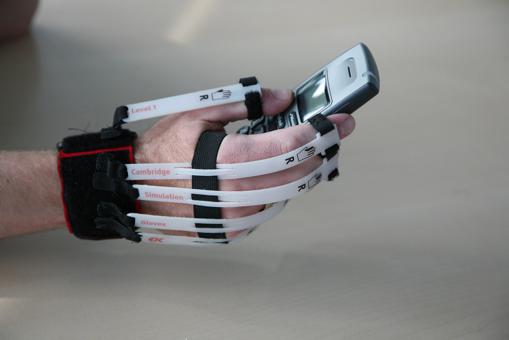 A man wearing a Cambridge simulation glove and holding a phone.