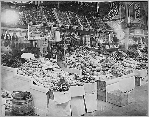 Young boy tending freshly stocked fruit and vegetable stand at Center Market, 02/18/1915 | by The U.S. National Archives