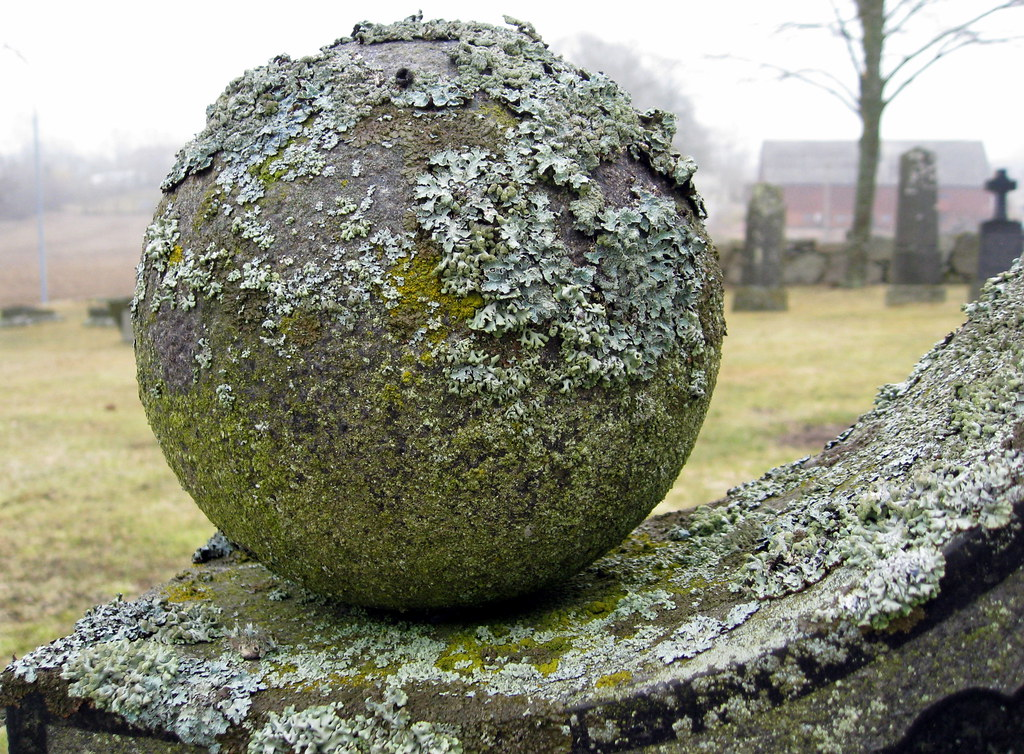 Stone ball with lichen seen on a gravestone at the for Large garden rocks for sale