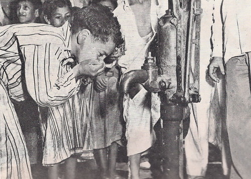 Iraqi child drink water from a mechanical waterpump 1955