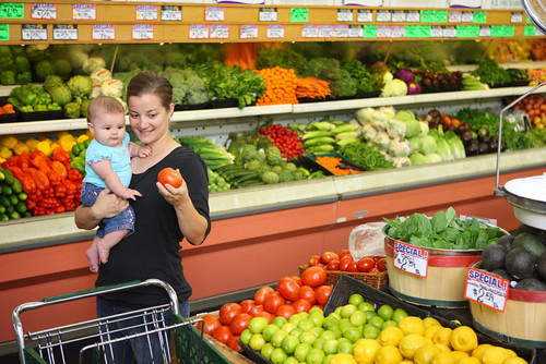 Young mother with baby selecting items in produce aisle of grocery store