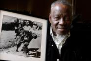 South African photographer Sam Nzima poses with the classic picture he took of Hector Pieterson being carried after martyrdom during the first day of the Soweto rebellion of 1976. | by Pan-African News Wire File Photos