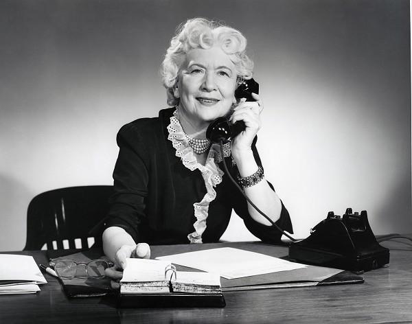 Woman Sitting At Desk Talking On Phone Mature Secretary