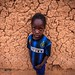 portrait of a little girl with the shirt of the inter football club in front of  great mud mosque in the bani, in the tribal region of the Sahel, northern Burkina Faso