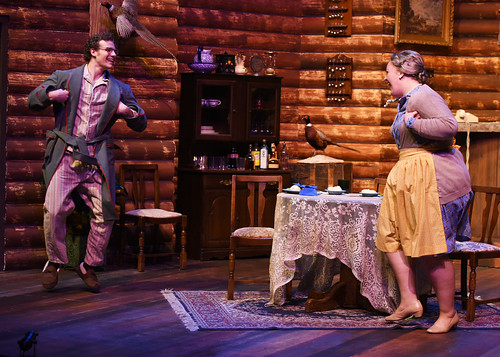 """An actor and actress flap their arms like birds while laughing during the play """"The Foreigner."""""""