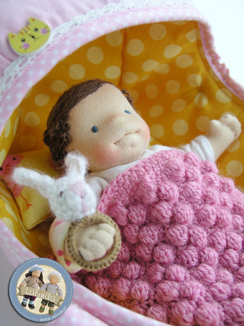 Tiny baby doll with a carrier