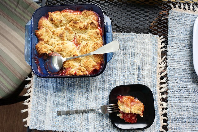 A scoop of strawberry cobbler sits on a small black plate, dwarfed by the rest of the pan in a bright blue baking dish next to it.
