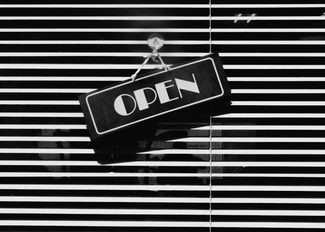 open sign hanging on barber shop door
