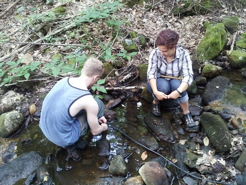 As part of Helton's research, Jason Sauer (M.S. student in NRE) and Eva Nelson (senior undergrad in Environmental Science) install field equipment to collect water samples in a Farmington River watershed stream.