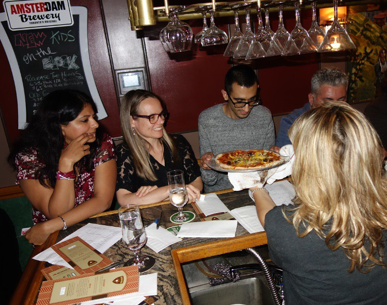 group examines pizza made by participant for makers' marks
