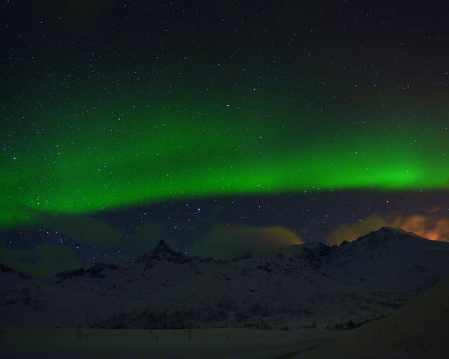 Auroras Boreales sobre montañas nevadas en Tromso, Noruega