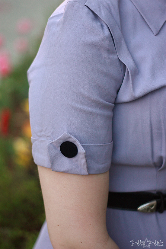 Detail of sleeve tab and velvet button on a purple vintage dress