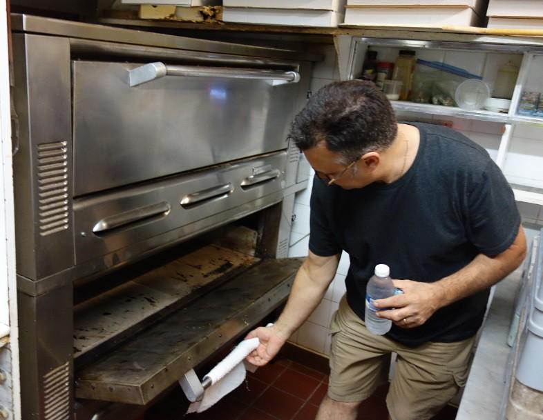 frankie checks the pizza oven