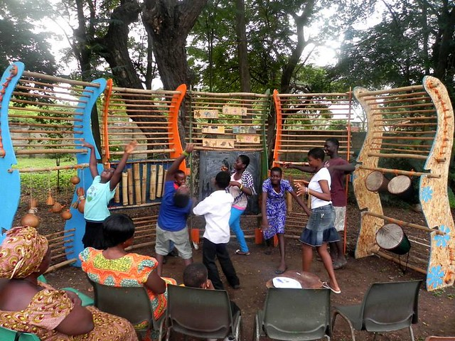 Children play and dance around the agoro structure in Mmofra Place.