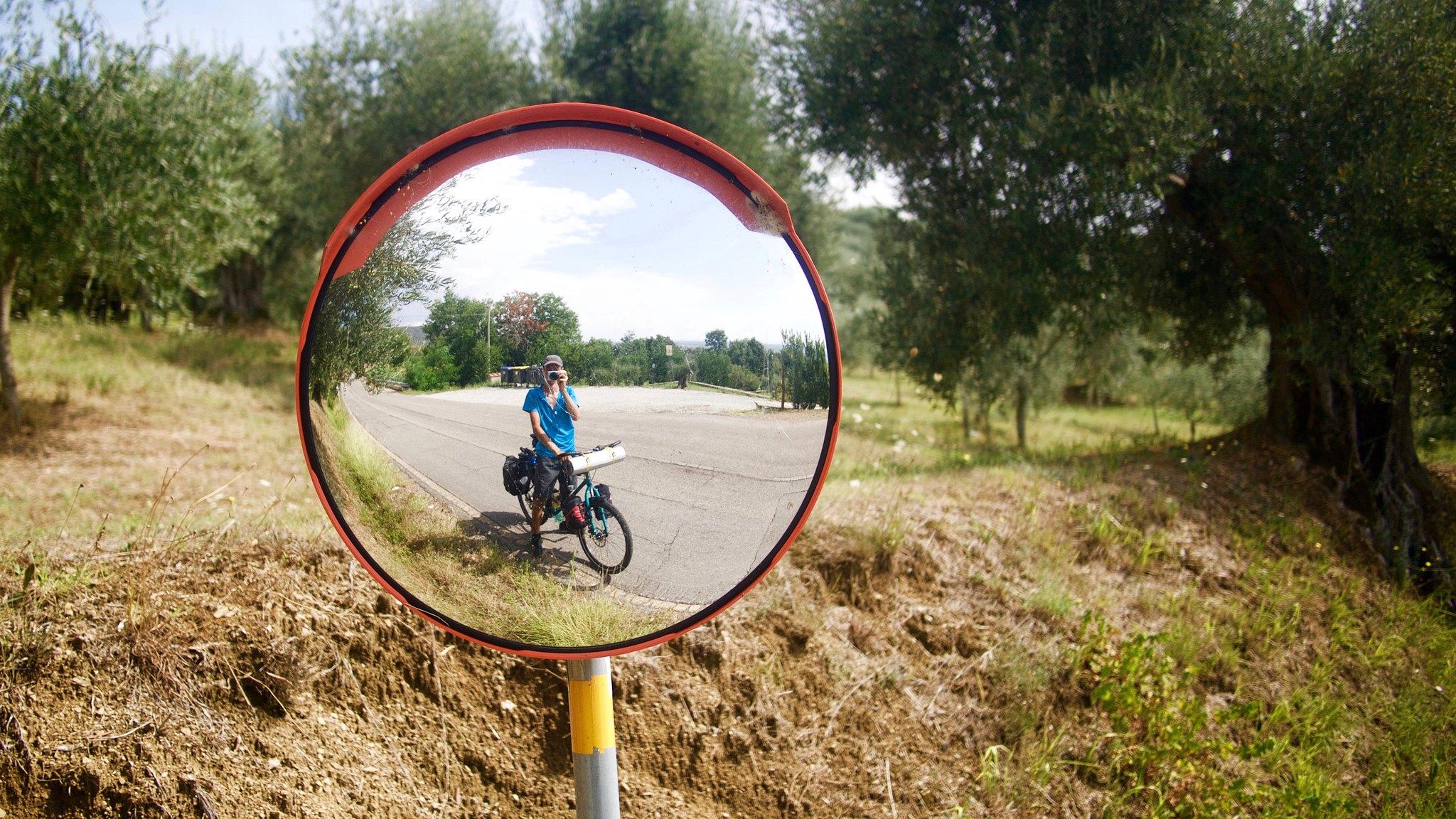 Odbicie rowerzysty w lustrze przy drodze