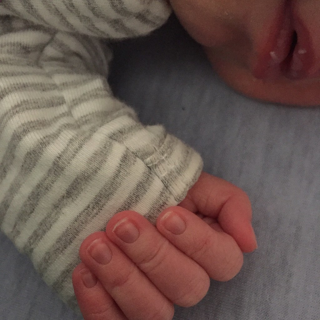 close up of baby hand and nails, with mouth and chin in background
