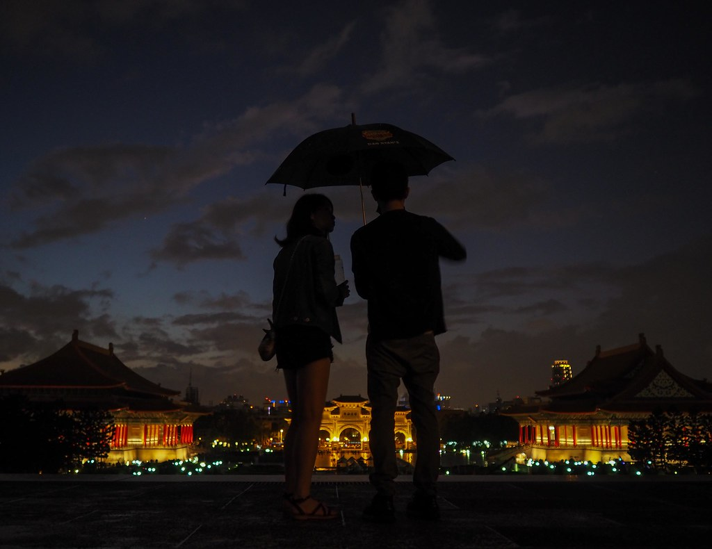 A young couple on the steps of the Chiang Kai-shek Memorial Hall on an autumn evening
