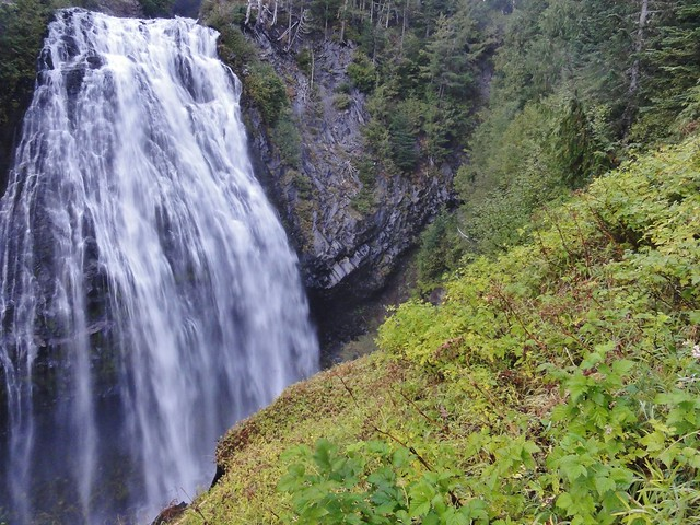 Image shows Narada Falls, a tall, wide cascade. It's towards the left. The andesite columns it flows over are visible to the right.