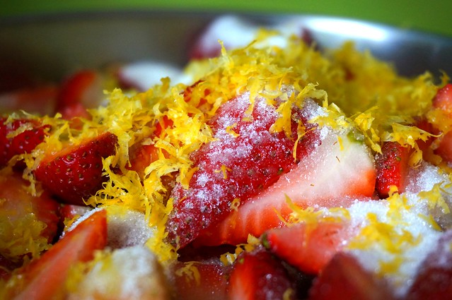 An extreme closeup of lemon zest and sugar scattered over halved strawberries.