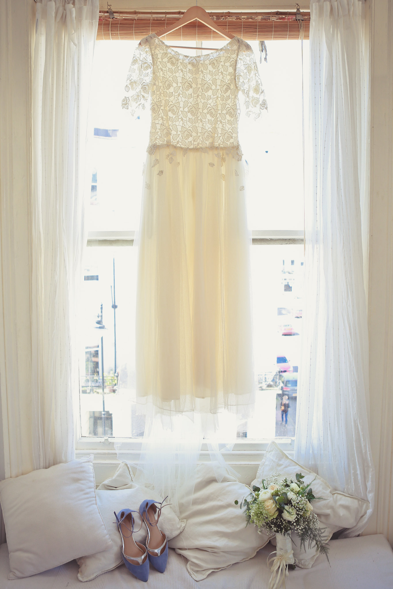 Tulle and Lace wedding dress hanging in a window