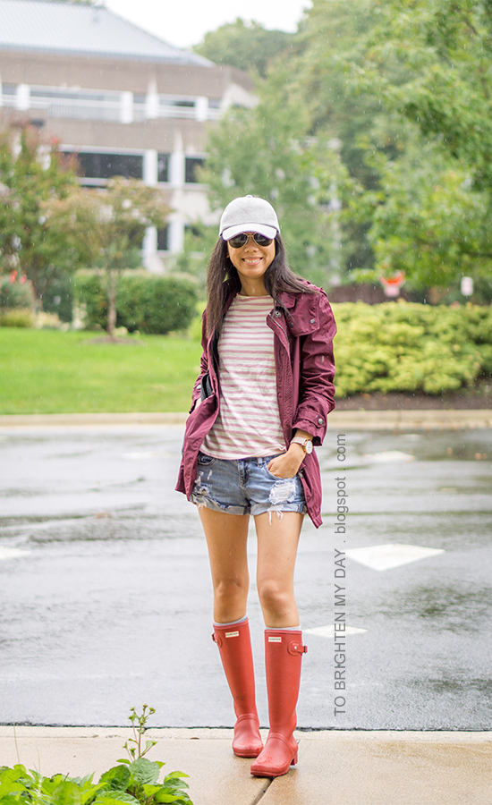 gray baseball cap, burgundy jacket, pink striped top, distressed shorts, oversized watch, red rain boots