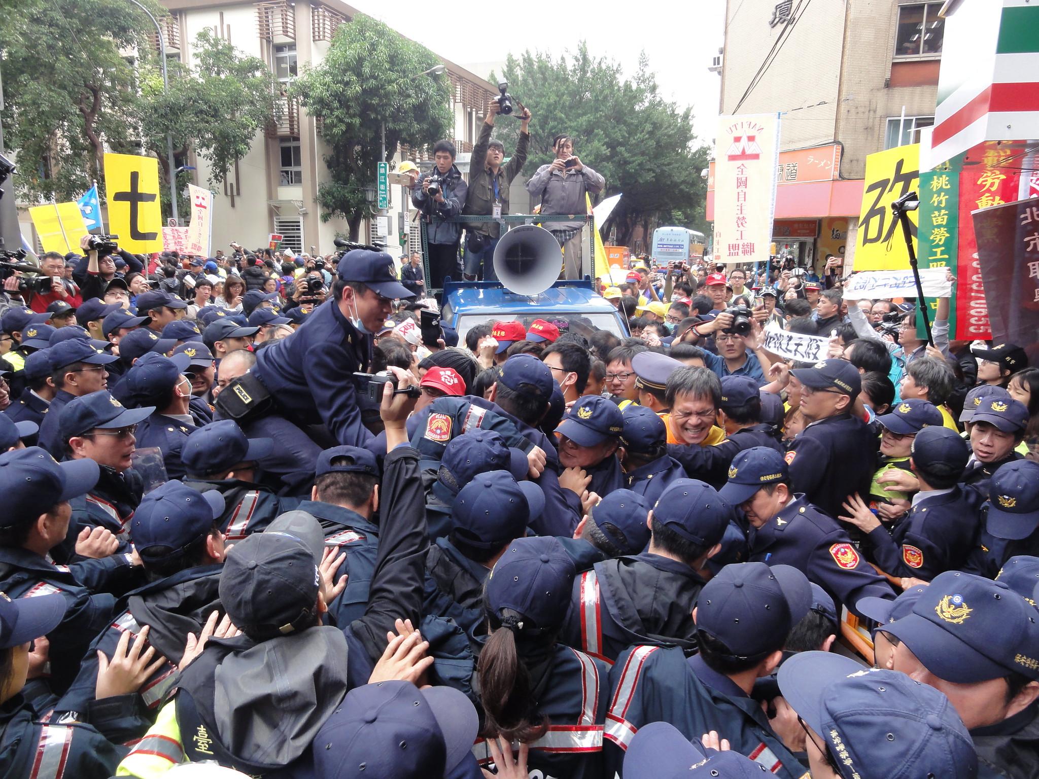 勞團百人聚集在立院青島東路側門,更多的警力則團團戒護。(攝影:張智琦)