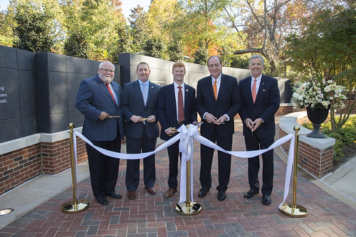 : A group of men are gathered with scissors to cut a ribbon in front of the Auburn Memorial