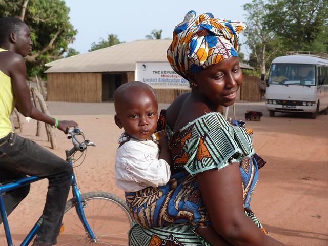 Mujer con bebé en una aldea pintada de Gambia