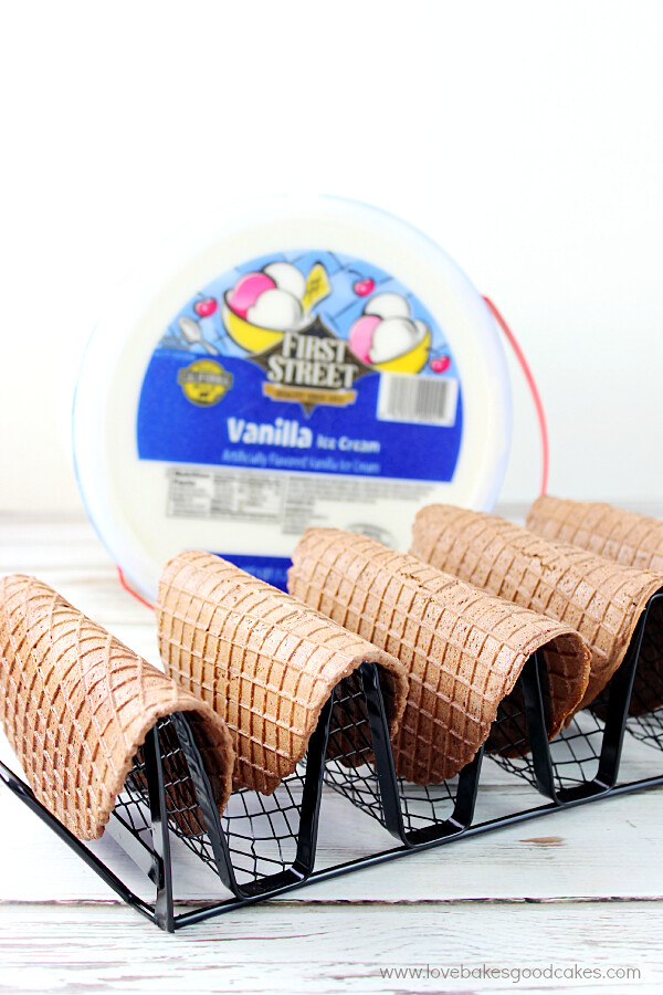 Chocolate taco shells on a taco stand with a gallon of ice cream.