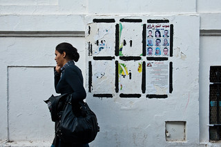 Woman walks by wall with election posters | by World Bank Photo Collection