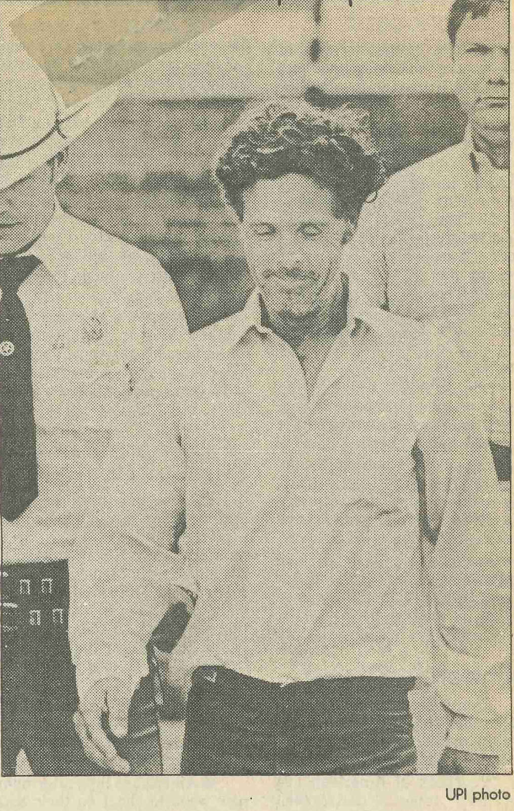 A picture of a photo from a newspaper clipping. Henry Lee Lucas is dressed in a light collared shirt and has an unshaven face. He is walking, with two officers behind him.