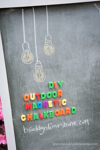 Left corner of outdoor chalkboard with hanging lights drawn out of chalk at the top and DIY Outdoor Magnetic Chalkboard spelled under them out of magnetic letters