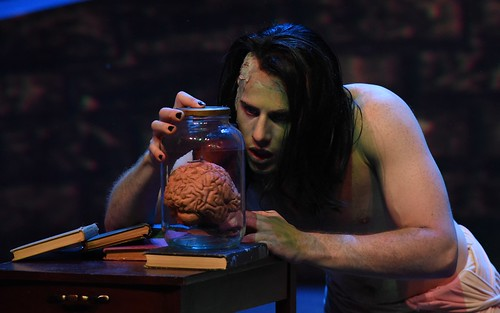 "A cast member of ""Frankenstein"" dressed as a monster is looking at a brain in a jar."
