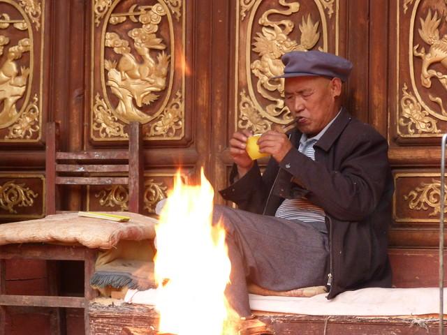 Hombre chino encendiéndose un cigarro (Yunnan, China)