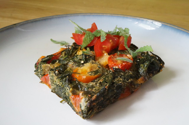 A square of oven frittata with hearty greens on a small plate, garnished with small bits of tomato and mint