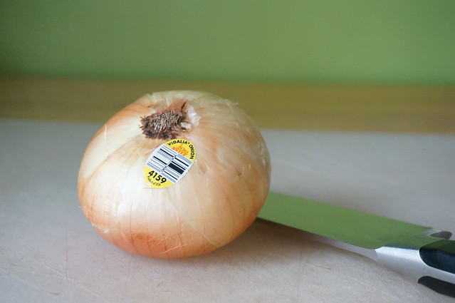 Vidalia onion glamour shot: a whole onion, with its produce sticker visible, in a soft-lit close-up